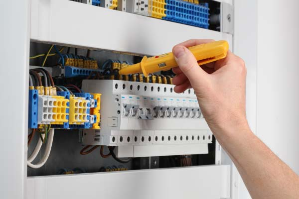 Hand of electrician in an electrical panel